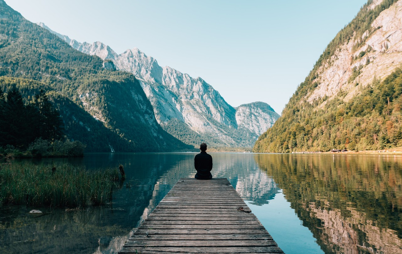 person sitting on a bank of a mountain lake